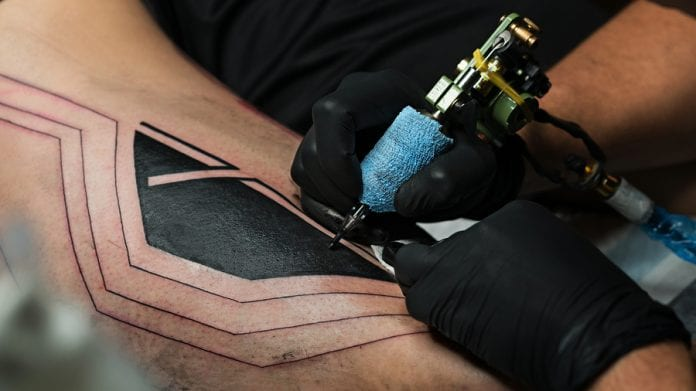 Professional tattoo artist uses a tattoo machine to make a tattoo on a man's leg.